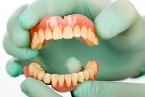Gloved hand holding dentures, Curry and Taylor DDS, 3815 Beck Road, St.Joseph, MO, 64506