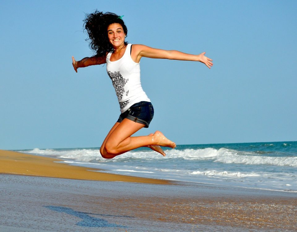 woman jumping at the beach, ocean in the background